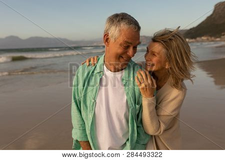 Front view of active senior couple embracing each other on the beach at dusk