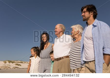 Low angle view of happy multi-generation family with arms around standing on beach in the sunshine
