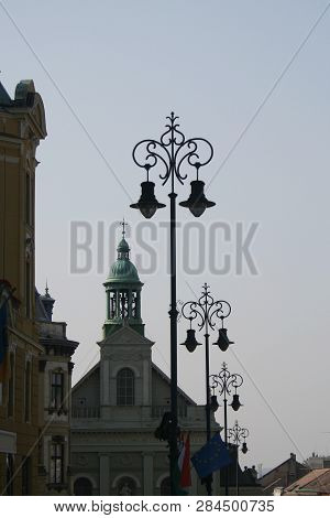 a cityscape of Pecs with ornate street lamps poster