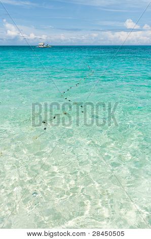 traditional fishing net in a clear blue tropical sea poster