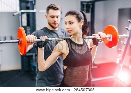 Fitness Girl Having Weight Training With Assistance Of Coach In Gym. Personal Fitness Instructor. Pe