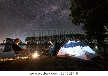 Night Camping On Lake Shore. Man And Woman Friends Sitting On Chairs Near Campfire And Illuminated T