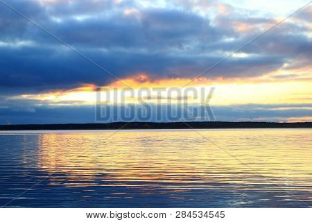 Beautiful sunset on the lake. Evening river landscape. Clouds reflected in the water. The horizon at sunset. Sea, lake at sunset. The waves on the river. The lake in Russia