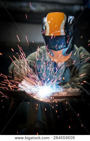 Industrial Worker At The Factory Welding Steel Construction