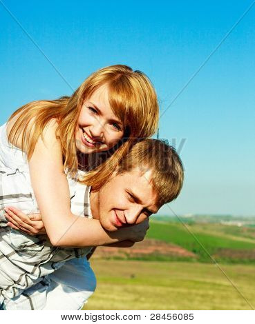 happy couple outdoor, young man giving his girlfriend piggyback ride