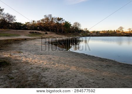 Small Dutch Lake With Sandy Beach During Sunset. The Photo Was Taken At The End Of A Sunny Day In Wi