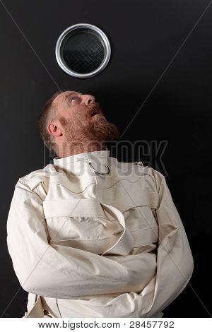 Hombre paranoico en una camisa de fuerza