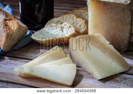 Cured Spanish Manchego Cheese With Red Wine Bottle