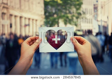 Health And Wellbeing Global Issue As Human Hands Holding A Paper Sheet With Heart And Cross Icon Ove