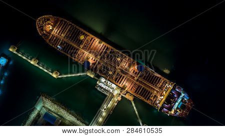Tanker Ship At The Port, Oil Terminal Tanker Ship Loading At Night, Aerial View.