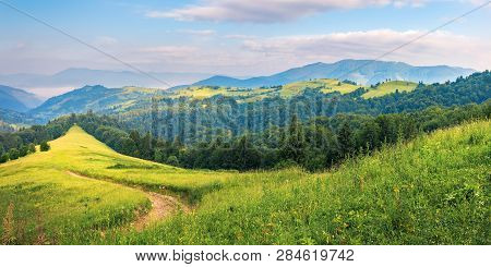 Panorama Of A Summer Countryside Landscape In Mountains. Winding Path Down The Grassy Slope Among Co
