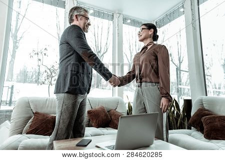 Dark-haired Elegant Woman In Grey Trousers And A Man In Eyeglasses Shaking Hands
