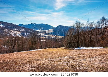Early Springtime In Mountainous Countryside. Leafless Trees On The Meadow With Weathered Grass And S