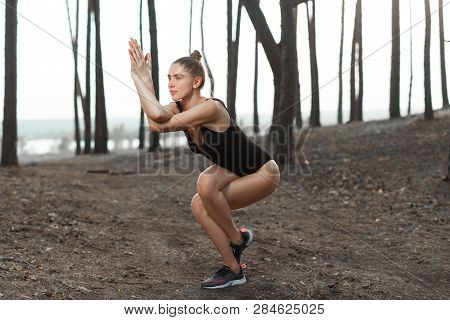 Beautiful Caucasian Girl In A Black Swimsuit Performs A Difficult Pose In Yoga In The Dark Evening F