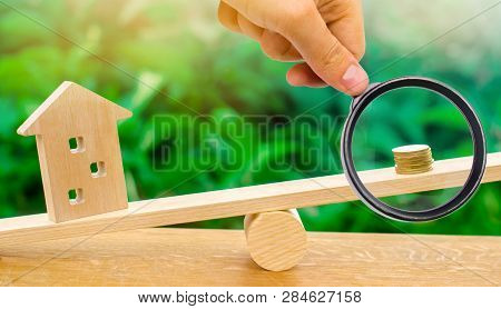 A Magnifying Glass Explores A Stack Of Coins On Scales And A Wooden House. Real Estate Concept. Deop