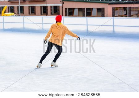 A Young, Slim Girl In Outdoor Figure Skating On A Roller Skating Rink