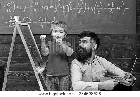 Kid Reciting A Poem While Teacher Listens Attentively. Cool Bearded Man In Pink Shirt Sitting On Flo