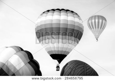 Grouping Of Three Hot Air Balloons Against Blue Sky In Vertical.