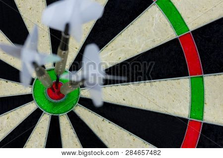 Three Darts Thrown At The Bulls Eye Of A Dartboard