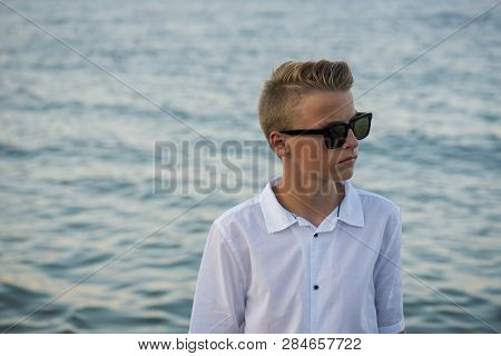 Wealthy Looking Kid On A Holiday Location With The Sea Behind Him.
