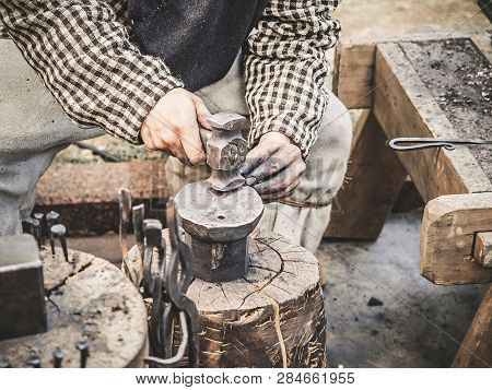 Blacksmith Hand With A Hammer On Steel Anvil . Hand Of A Blacksmith With Hammer Close Up. The Blacks