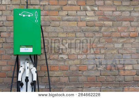 Electric Cars Charging Concept. Electric Vehicle Charger Station Installed On Vintage Brick Wall. Mo