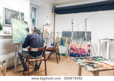 Talented Artist Sits On A Chair In A Cozy Artistic Studio And Paints An Oil Painting. Creative Atmos