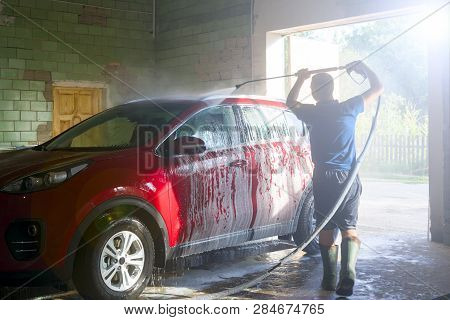 Shot Of A Man Washing His Red Car Under High Pressure Water. Car Cleaning. High Pressure Water Washi