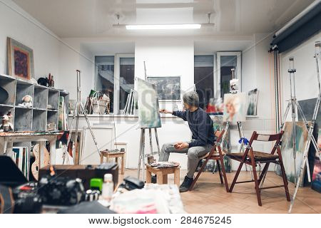 Painter Sits On A Chair In A Cozy Studio And Works On A Painting, Drawing Oil Paintings. Artist Work