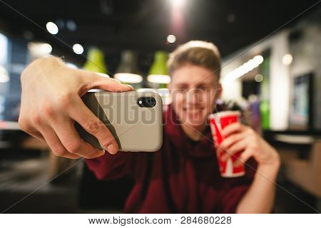 Young Man With A Drink In His Hands Makes A Selfie In A Fast Food Cafe, A Smartphone Close-up And In