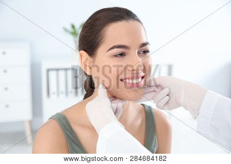 Dermatologist examining patient's face in clinic. Skin cancer checkup poster