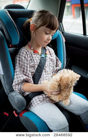 The Little Girl Sits In A Car