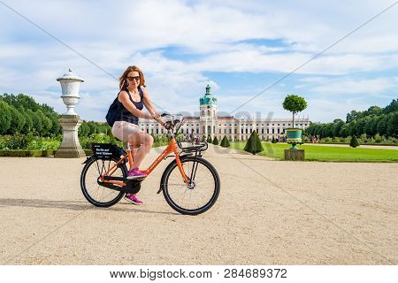 Berlin / Germany - 29 June 2018: Happy Girl On Rental Bicycle, Posing In Front Of Charlottenburg Pal
