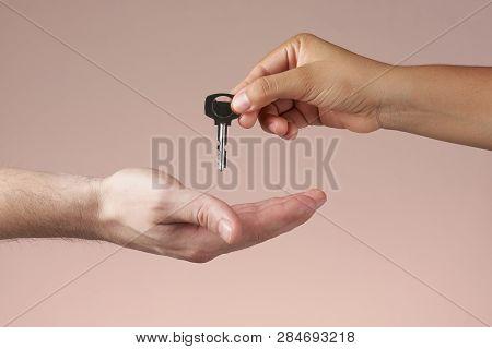 Woman Hand Handing Key To Man Hand. Hand Giving House Or Room Key.