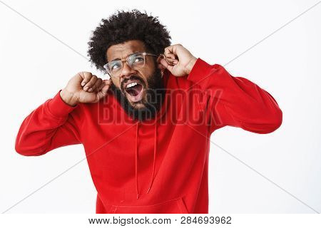 Studio shot of disturbed guy suffering from discomfort as compaining on loud neighbours being irritated by noise and annoying music yelling closing ears with index fingers, stooping, looking up poster