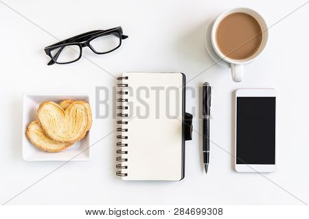 Cup Of Coffee With Snacks, Mobile Phone And Notebook On Desk Office With Copy Space, Top View