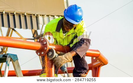 Tradesman Working With An Angle Grinder On A Building Site