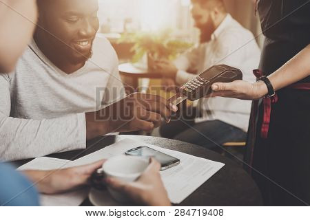 Young African American Is Calculated Credit Card. A Smiling African American Man Is Paying For An Or
