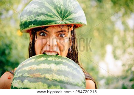 Very Ridiculous Girl Writhes Her Face Holding Two Halves Of Watermelon. Silly Girl Makes A Funny Fac