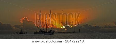 Picturesque Orange And Yellow Sunset Panorama At Sea Over Water And Through Beautiful Cumulonimbus C