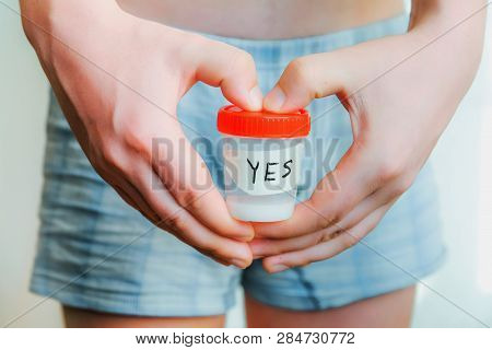 A Man In Shorts Holds A Sperm Analysis With The Words Yes. Hands In The Shape Of A Heart. Close-up O