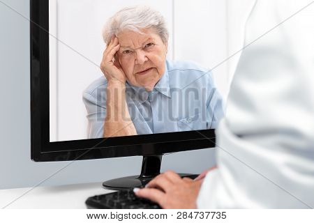 Telemedicine And E-health With A Doctor And A Elderly Woman With Afflictions, Patient On The Desktop