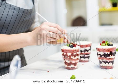 Decoration Of The Finished Dessert. Pastry Chef Sprinkles Confectionery With Yellow Powder. The Conc