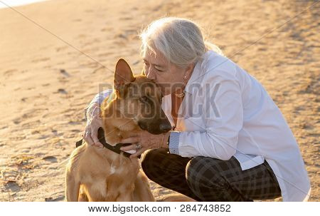Portrait O Happy Attractive Senior Woman With Her German Shepard Dog On The Beach At Autumn Sunset