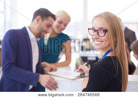 Sales situation in a car dealership, the young couple is signing the sales contract to get the new car