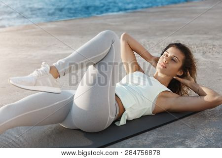 Good-looking Caucasian Young Sporty Woman Runner Workout Before Jogging Lying Mat, Concrete Quay Loo