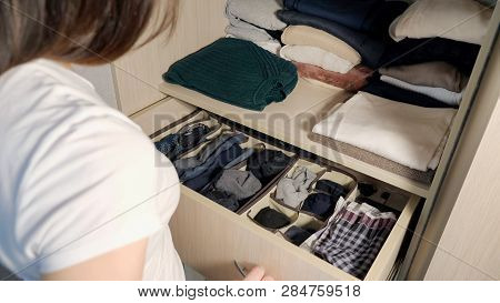 The Drawer With Underwear In The Closet. Girl Organizing Clothes In Wardrobe, Close Up.