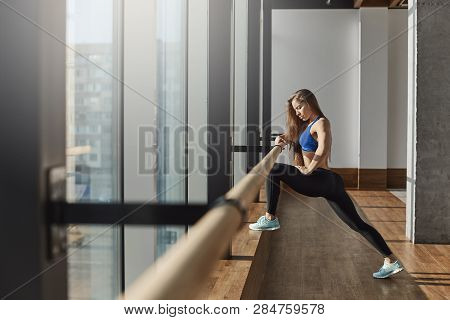 Young Motivated Determined Woman In Sportswear Sports-bra Leggings Stretching Legs On Ballet Barre S