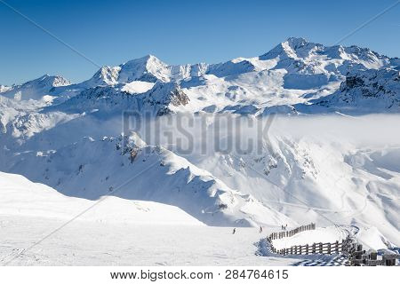 Unidentified Skiers Skiing On A Ski Slope In Pristine Alpine Landscape. Calm And Tranquil Winter Sce