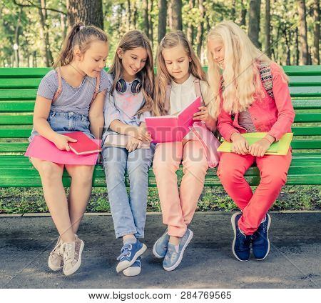 Pretty smilng little girls holding notebooks and read together sitting on the green bench in the park